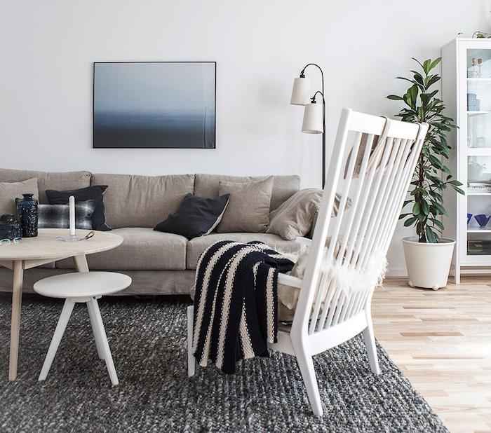 inspiration scandinave, parquet de bois, grande chaise en bois peinte en blanc, canapé en tissu beige avec coussins décoratifs