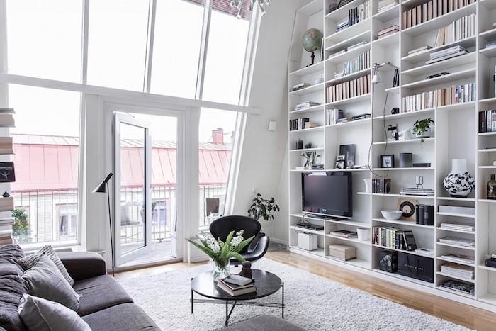 deco nordique, petite table basse en noir, chaise en noir, canapé en tissu gris foncé avec coussins décoratifs, bibliothèque murale en blanc