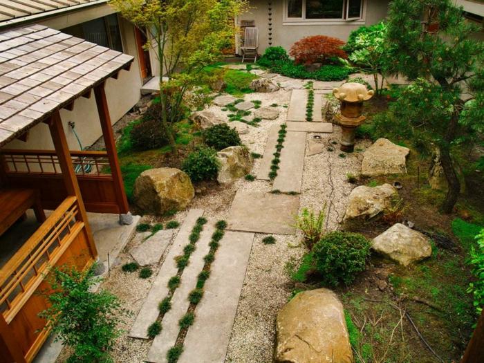 decoration zen dans le jardin, sol en gravier, chemin entouré de pierres, arbres et arbustes verts