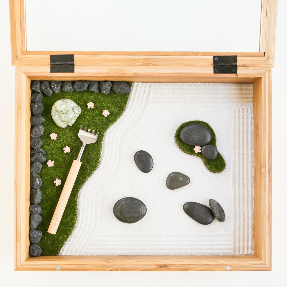 idée comment fabriquer un jardin zen miniature dans une boite à thé. sable fine, galets, statuette zen et rateau, mousse artificiel