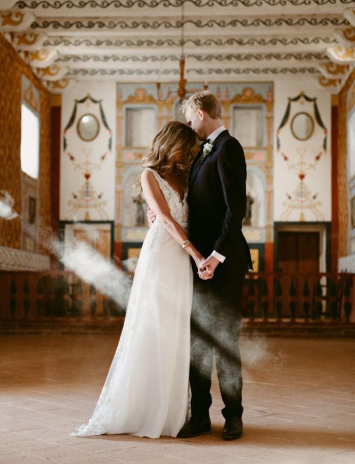 une photo de couple qui partage un moment intime dans une salle vide, un rayon de lumière perçant pour une ambiance magique