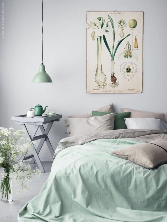 chambre vert d eau, couverture de lit et lampe vert clair, linge de lit gris et vert, mur couleur gris perle et table de nuit grise, deco murale affiche végétal
