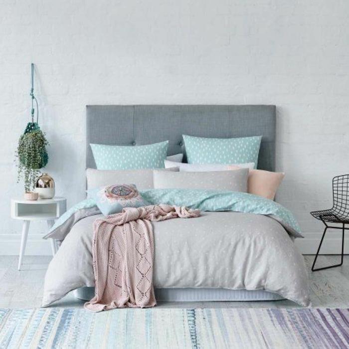 lit gris, couvert de linge de lit couleur vert pastel aqua, gris et rose, tapis à rayures couleurs usées, mur en briques blanches, tête de lit grise, plante suspendue