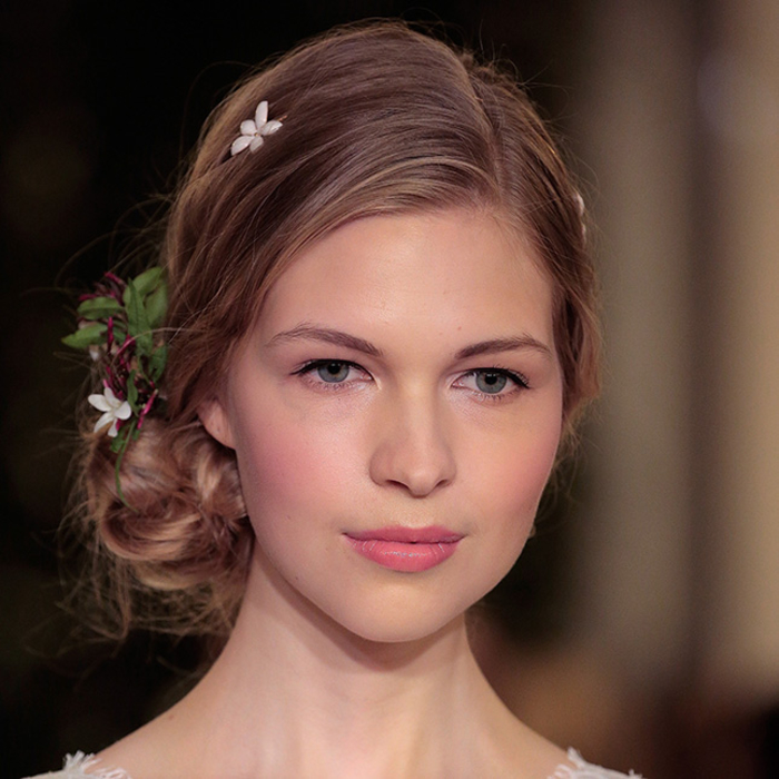 une vision de mariée romantique réalisée avec un maquillage discret aux nuances de rose complétée par un chignon bas décoré de fleurs