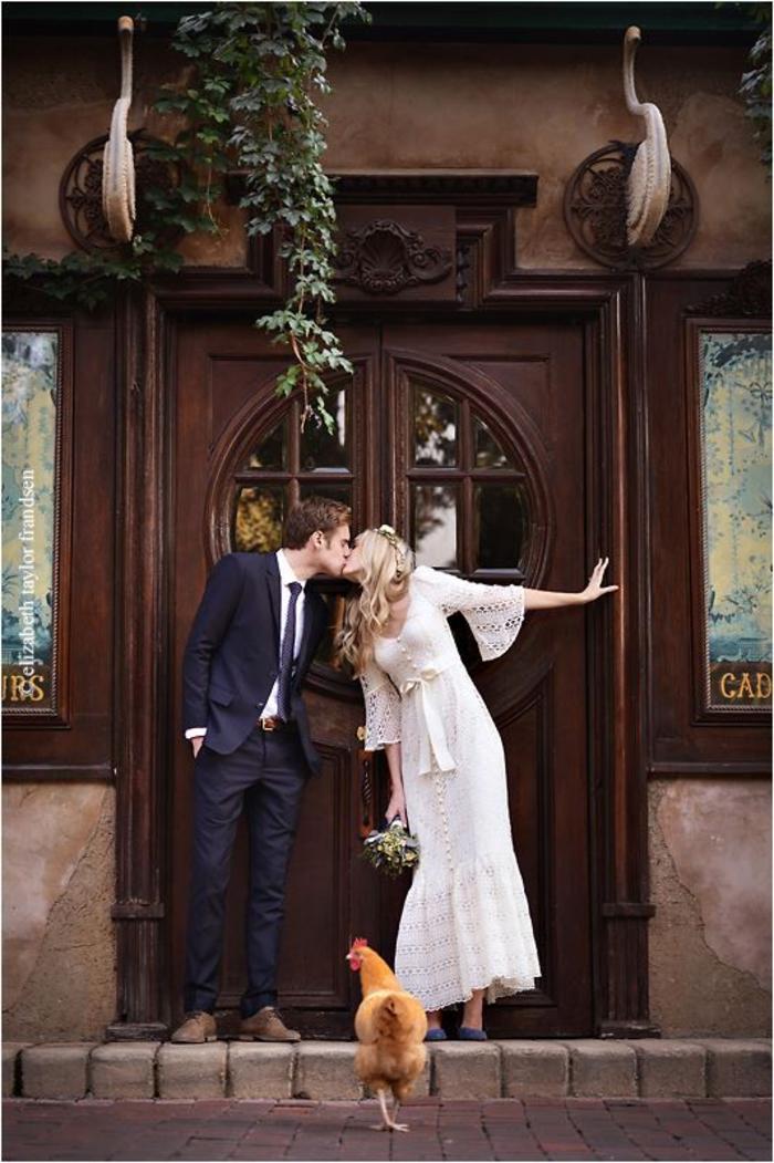 un mariage original d'esprit bohème chic, photo de couple de mariée avec une poule en premier plan