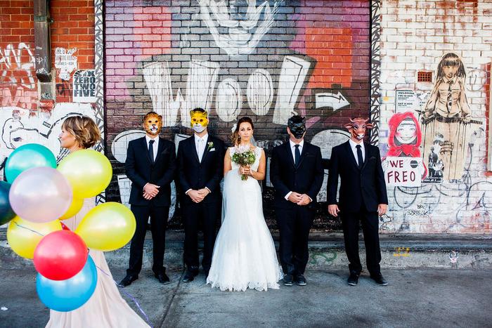 une séance photo originale avec des masques tête d'animal, toile de fond originale graffiti art sur un mur en briques