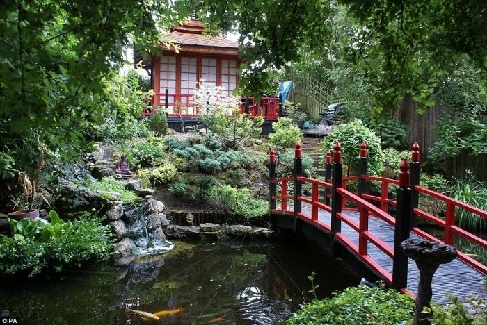 maison japonaise, végétation en pente, un petit pont en rouge et noir, petit étang carpe koi, arbres et arbustes