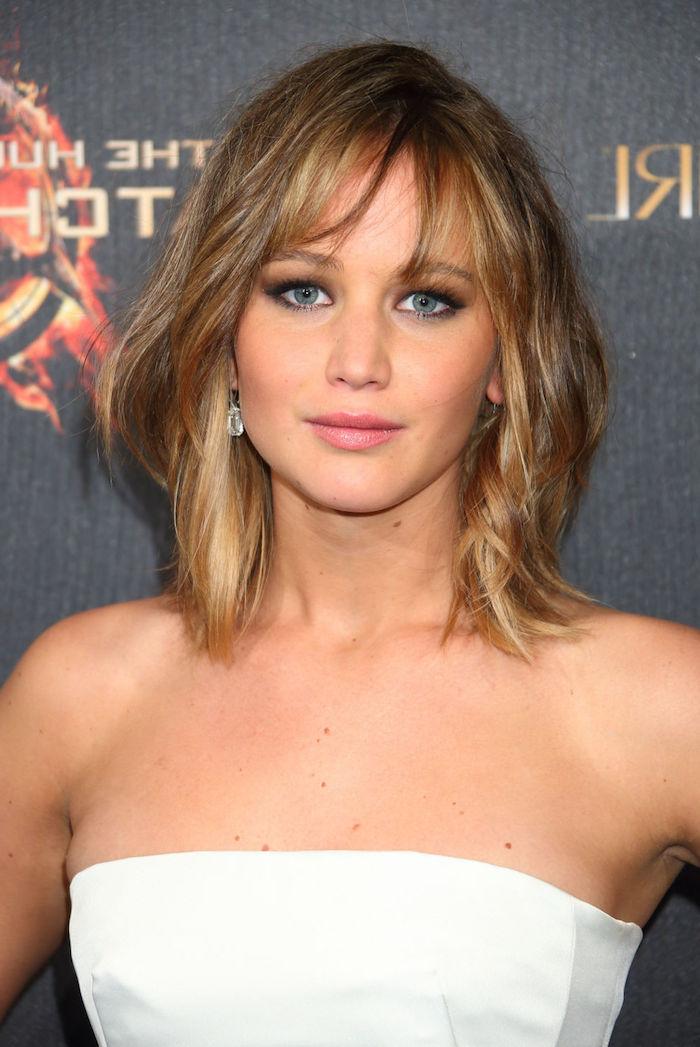 coloration cheveux, Jennifer Lawrence, coupe de cheveux mi longs avec racines foncées et extrémités en blond dore, robe blanche avec bustier