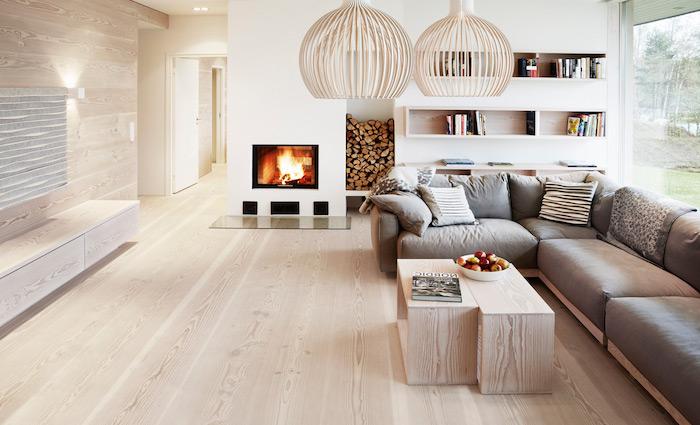 inspiration scandinave, parquet en bois clair, canapé d'angle en gris avec coussins, suspension luminaire beige