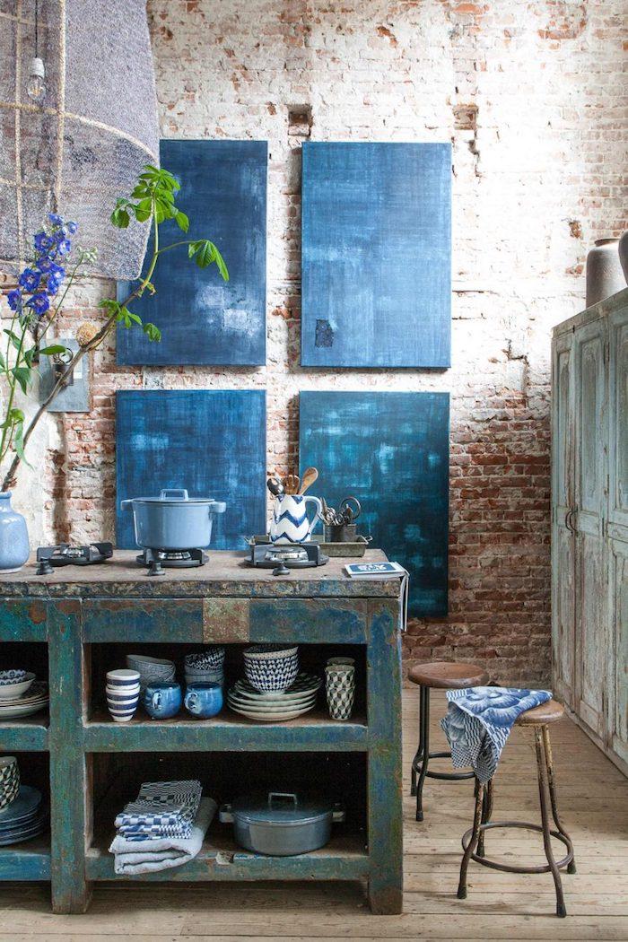 motif géométrique, aménagement cuisine vintage, tableau en bleu foncé, murs en briques, tabouret en cuir et fer