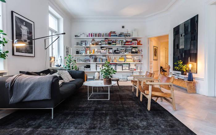 deco esprit scandinave, bibliothèque à livres et objets décoratifs, canapé noir avec coussins, table basse en blanc, chaises en bois