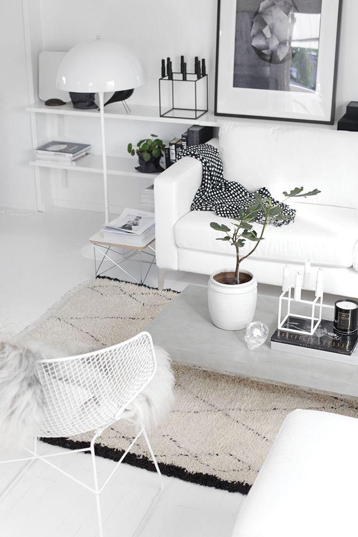 inspiration scandinave, tapis beige à lignes noires, chaise blanche avec housse en faux fur, lampe sur pied blanche