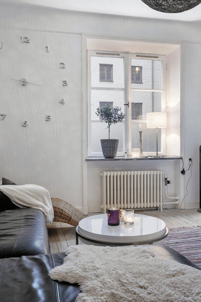 deco esprit scandinave, murs peints en blanc, horloge grand, parquet en bois clair, table ronde blanche