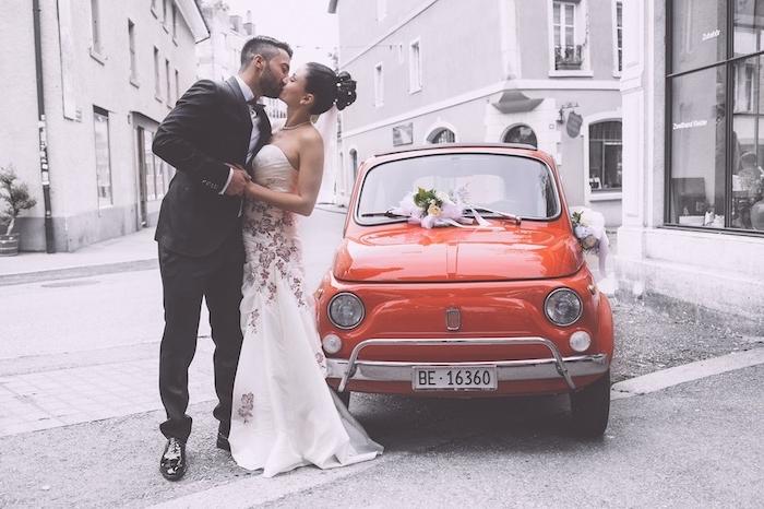 chignon marriage, couple de jeunes mariés, robe de mariée à motifs floraux, coiffure mariée