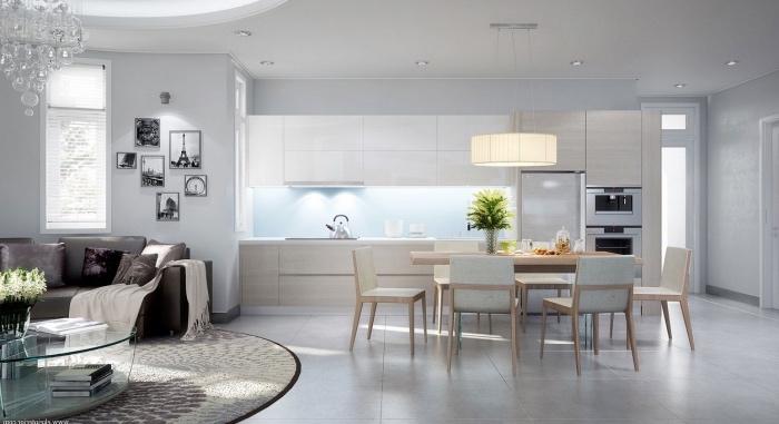 amenagement petite cuisine ouverte sur une salle à manger avec façade cuisine en bois clair, crédence bleu, salle à manger avec des chaises et table en bois, revêtement sol carrelage gris, salon avec tapis et canapé gris, table basse en verre