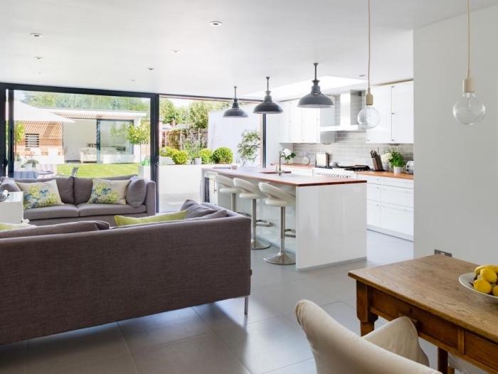 modèle de cuisine ouverte sur salon, façade cuisine et ilot central blanc avec plan de travail en bois, carrelage gris, canapés gris et coussins fleuris, plusieurs suspensions design