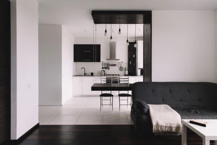 modele de cuisine semi ouverte en noir et blanc, aspirateur inox, table et chaises noires, carrelage blanc, salon parquet marron foncé, canapé noir, table basse blanche