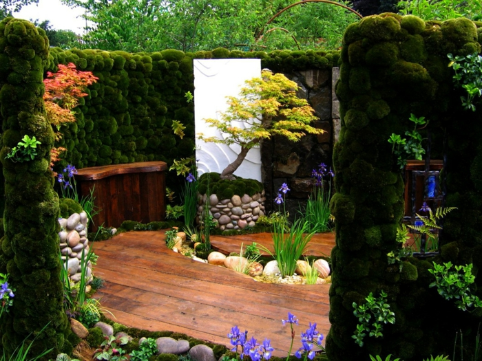 un coin détente cloisonné d un mur de mousse verte, sol et banc en bois, arbre et fleurs fraiches, pauysage paradisiaque