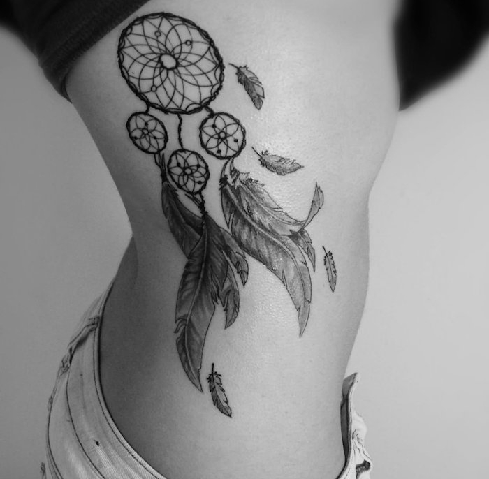 tatouage femme, dessin en encre sur le corps féminin, tatouage à design attrape rêve avec plumes