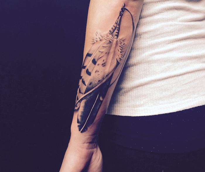 plume tatouage, tenue en débardeur blanc et pantalon noir, tatouage sur le bras en design plumes