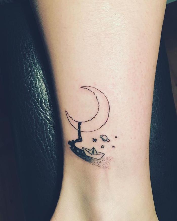 un tatouage minimaliste ciel et mer avec un petit bateau en origami et un croissant de lune graphique