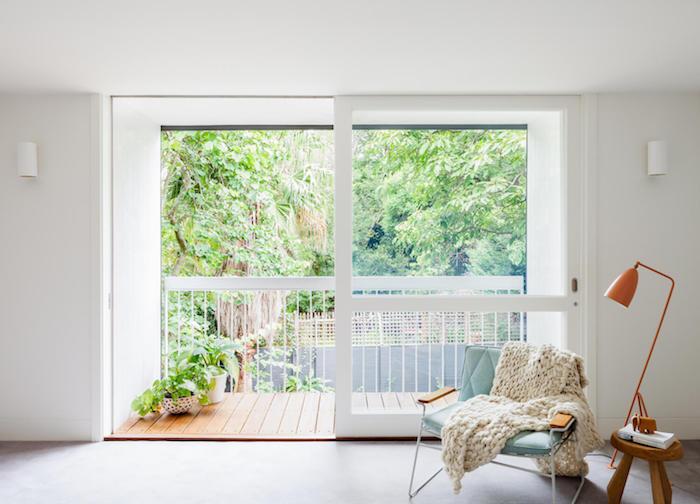 décoration scandinave, porte coulissante vers le balcon, lampe sur pied orange, plafond et murs blancs