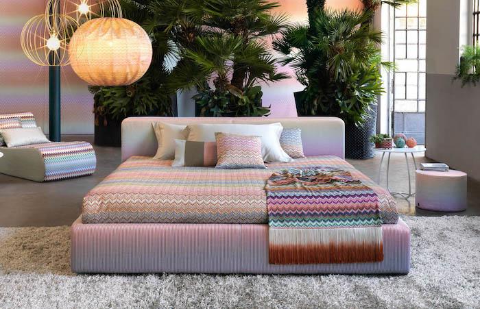motif géométrique, lit king-size en rose pastel, couverture et linge de lit à motifs géométriques, plantes vertes tropicales