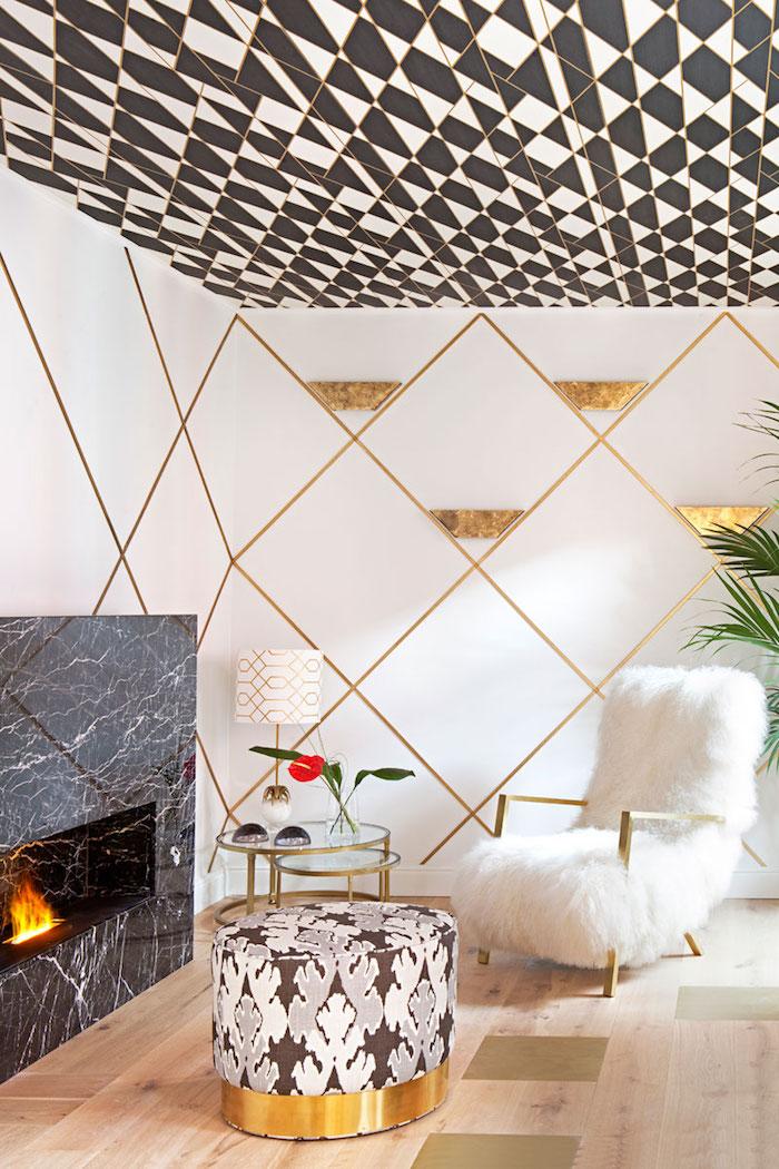 papier peint motifs géométriques, cheminée noire, table basse en verre et laiton, plafond en blanc et noir avec lignes dorées