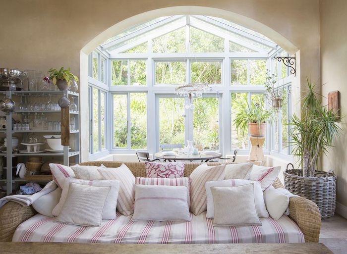 canapé en rotin, coussins d assise rouge et blanc, coussins blanc et rouge, vaisselier en metal sur le fond, panier en rotin, palmier, grandes fenêtres