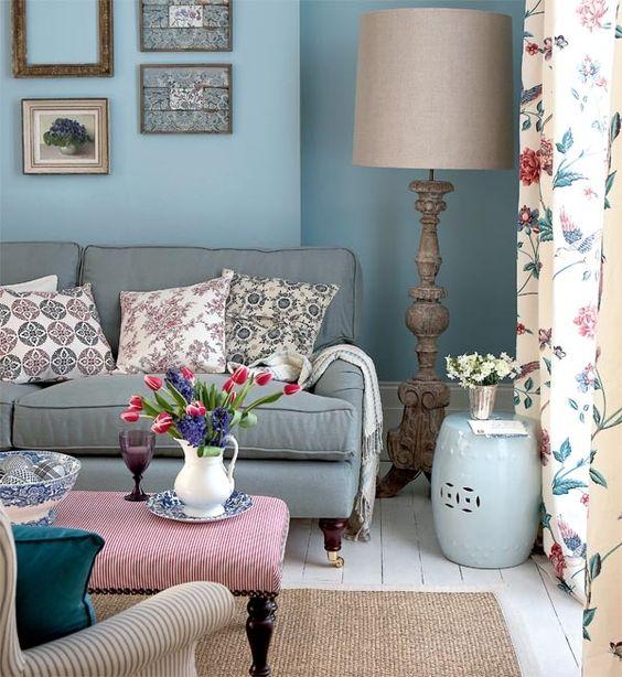 amenagement salon shabby chic avec mobilier vintage, canapé shabby chic bleu-gris, table et lampe vintage, decoration murale de cadres, parquet blanchi, coussins et rideaux fleuris