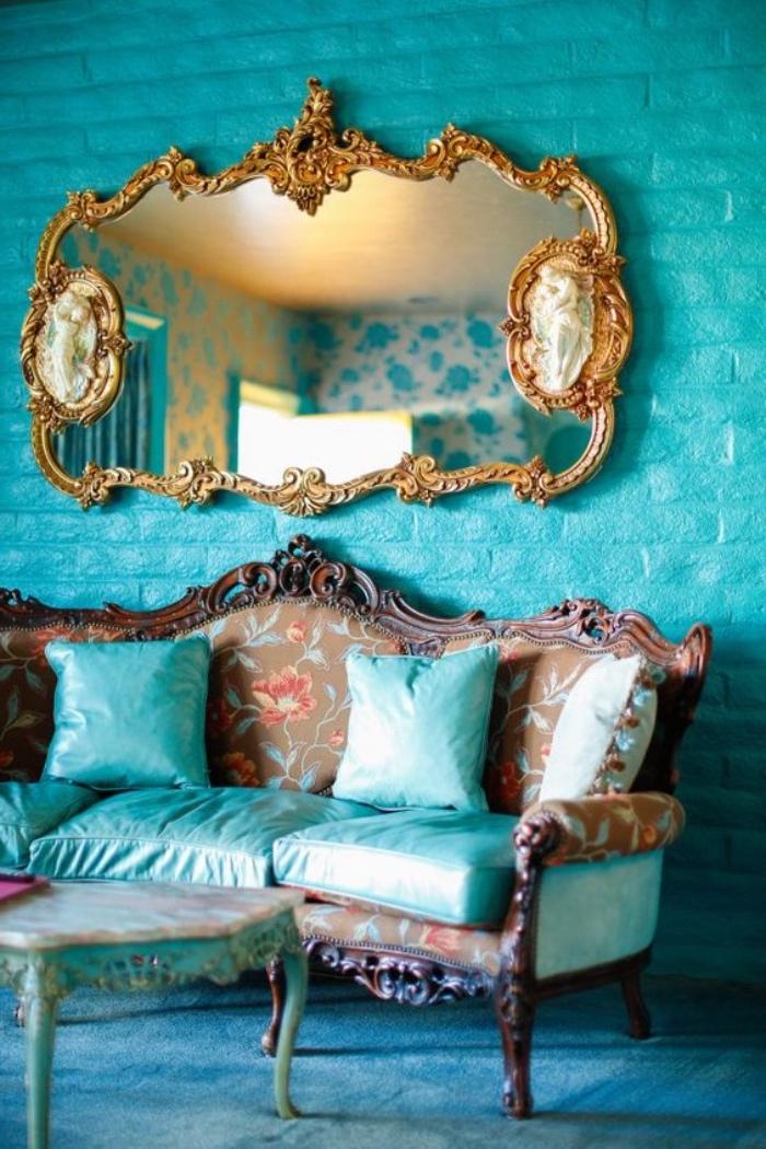 idée de décoration murale peinture vert d eau foncé et canapé baroque avec coussins décoratifs et d assise vert pastel, table basse vintage, tapis bleu et miroir baroque