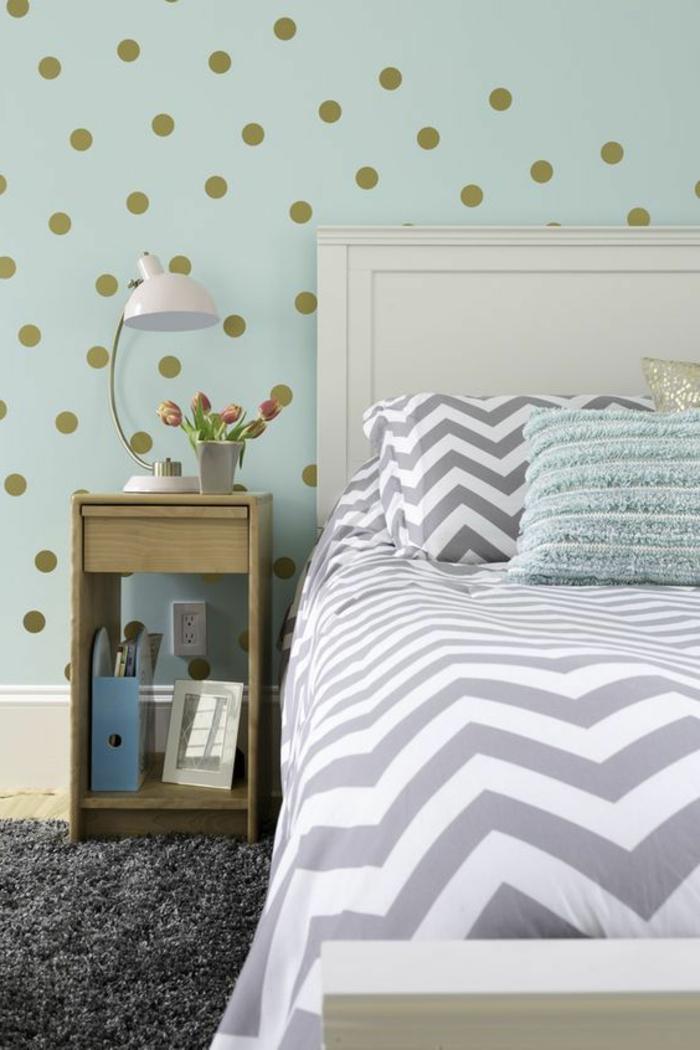 chambre, mur peinture vert d eau à pois dorés, tapis gris anthracite, linge de lit blanc et gris, table de nuit en bois
