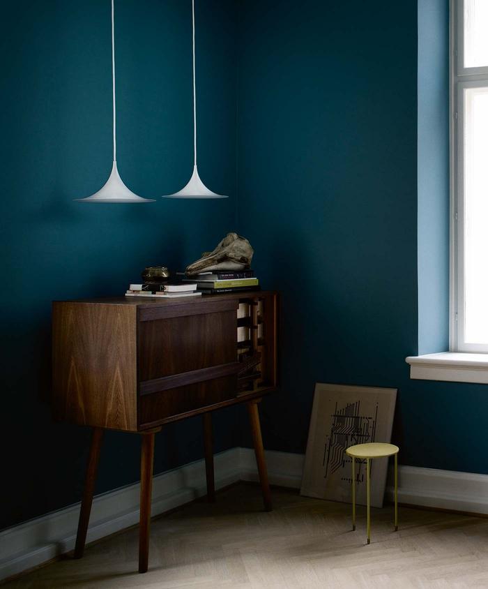 des lampes en suspension au design épuré et ultra léger sur un fond en bleu paon profond