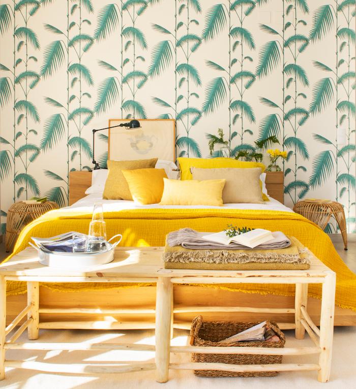 oasis tropical, aménagement chambre à coucher, lit king size avec couverture et coussins jaunes, papier peint à motifs tropicales