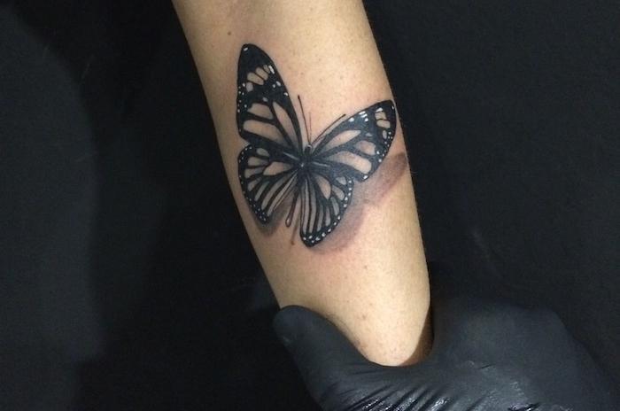 tatouage avant bras femme, tatto 3d à motif papillon noir, idée dessin en encre sur la peau pour femme