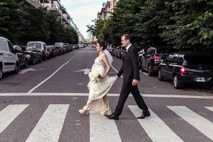 photo artistique de couple de mariés qui traverse un passage piétons