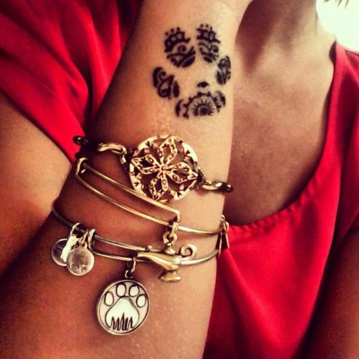 patte de chat tattoo, empreinte de chat noire aux motifs ethniques et bracelets