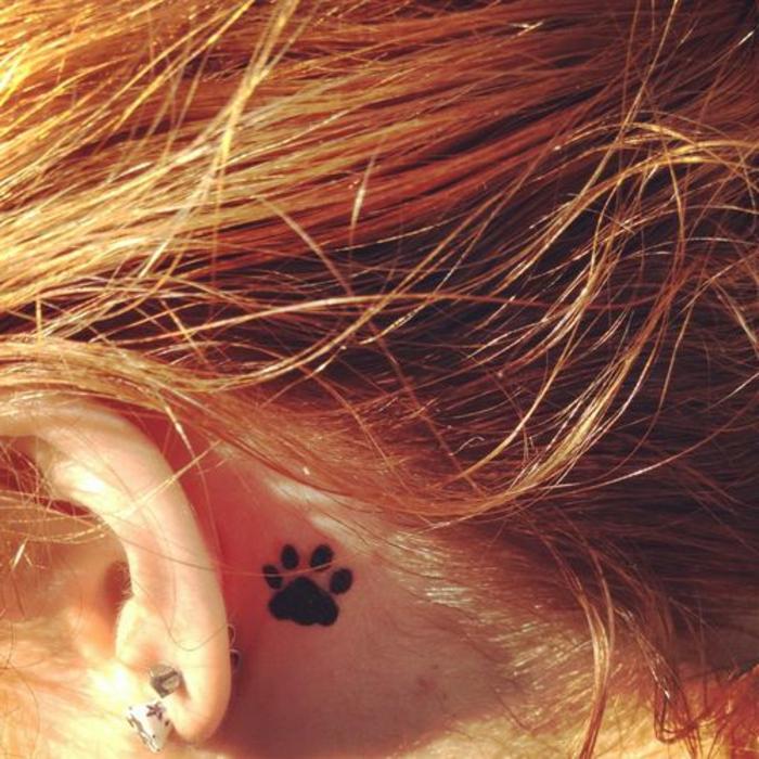 patte de chat tattoo, tatouage derrière l'oreille avec de l'encre noire