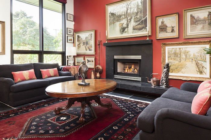 salon aux murs rouge corail et meubles noirs