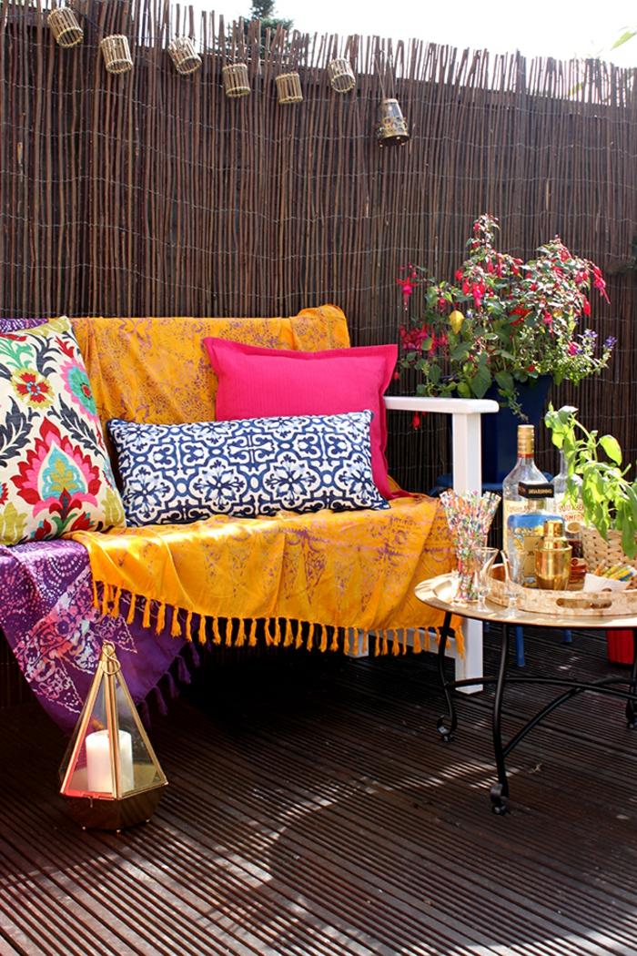 couleur magenta dans le jardin ou la terrasse avec meuble plein de coussins colores