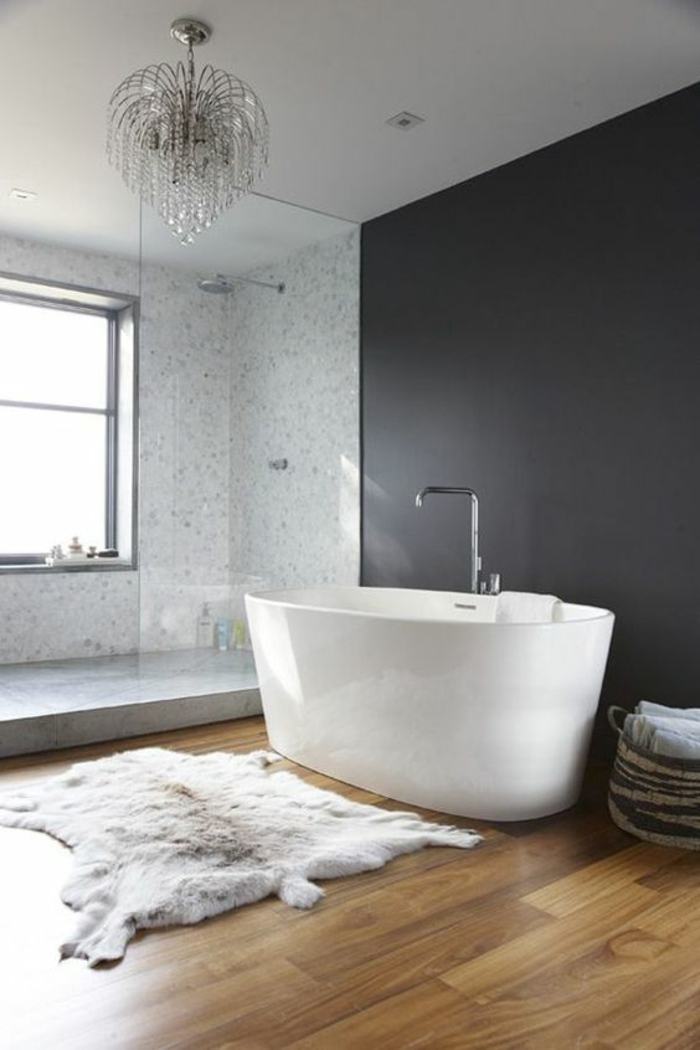 gris perle salle de bains avec baignoire blanche ovale lustre baroque au plafond parquet nuancé en PVC