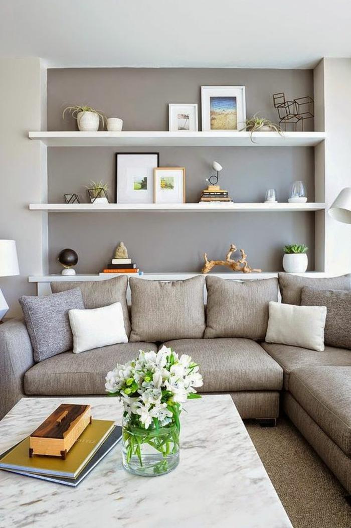 gris perle dans le salon avec des étagères blanches aux mini tableaux avec une basse table en marbre