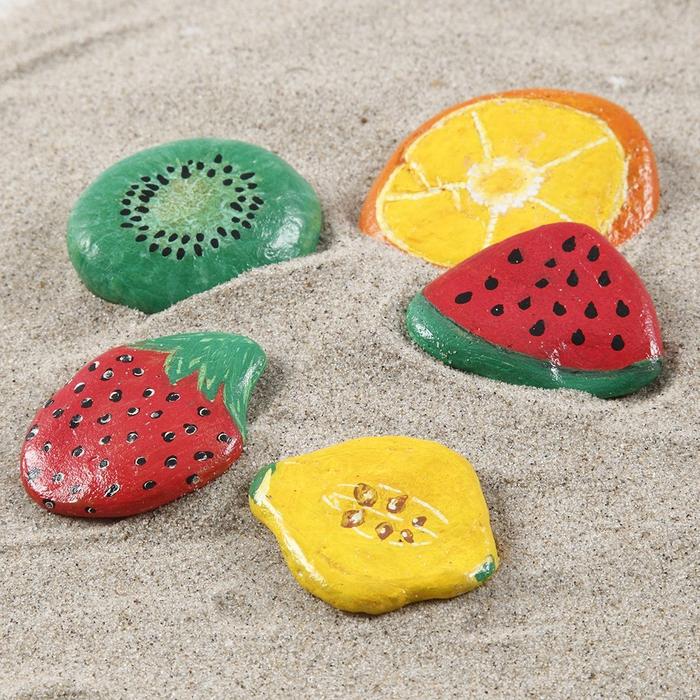 des fruits tropicaux aux couleurs vitaminées dessinés sur des galets décoratifs, idée pour des activités manuelles maternelles pendant les vacances d'été