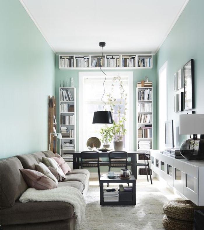 salon vert d eau avec canapé gris et coussins rose et gris, tapis blanc cassé, meuble télé blanc design, bibliothèque blanche, bureau et chaise gris anthracite