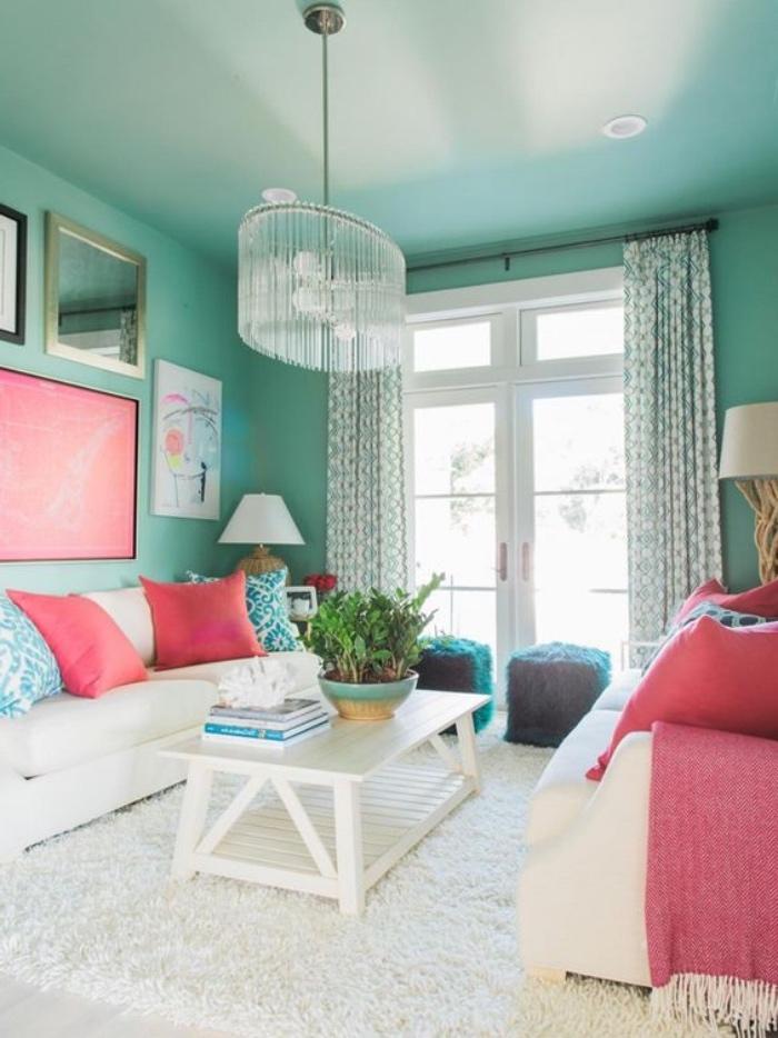 modele de salon vert d eau, peinture murale vert celadon, tapis blanc et table basse blanche, canapés blancs et coussins rose, bleu et blanc, lustre élégant