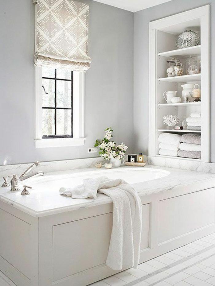 petites salles de bains avec grande baignoire en blanc et des espaces rangement aux étagères insérées dans le mur