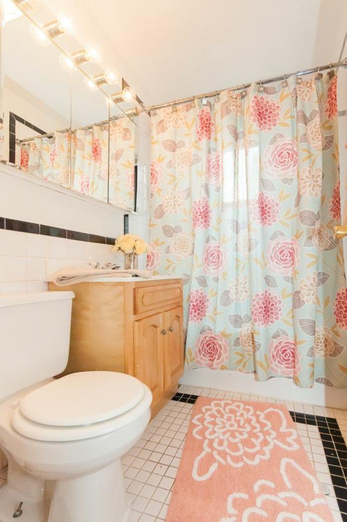 salle de bain très petite aux rideaux baignoire et tapis en fleurs couleur corail