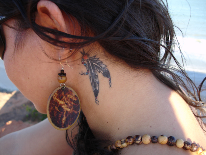 tatouage femme, cheveux longs en nuance marron foncé, boucles d'oreilles en bois
