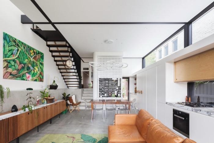 petite cuisine équipée avec façade cuisine blanche, plan de travail en marbre, revêtement sol effet béton, canapé en cuir marron, tapis vert, meuble en bois, coin salle à manger avec table et chaises