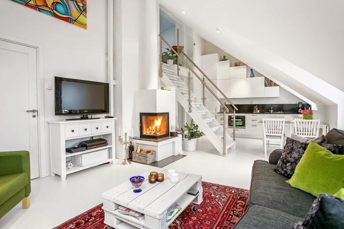 petite cuisine équipée avec façade cuisine blanche et crédence gris anthracite, revêtement sol blanc, canapé gris et table basse en palette, tapis oriental, fauteuil et coussin vert, cheminée romantique, coin repas